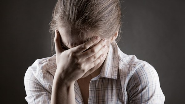 Young crying woman on a dark background