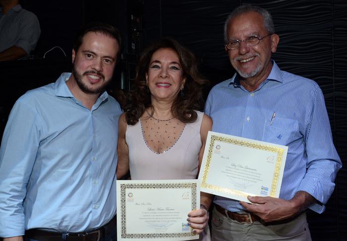 Alex Mendes, presidente do Santos e Região CVB, homenageam Lucia Teixeira, presidente do conselho, e Luiz Dias Guimarães, secretário de Comunicação da Prefeitura de Santos