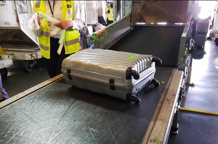 Os funcionários das analisam as etiquetas e então encaminham as bagagens para os contêineres
