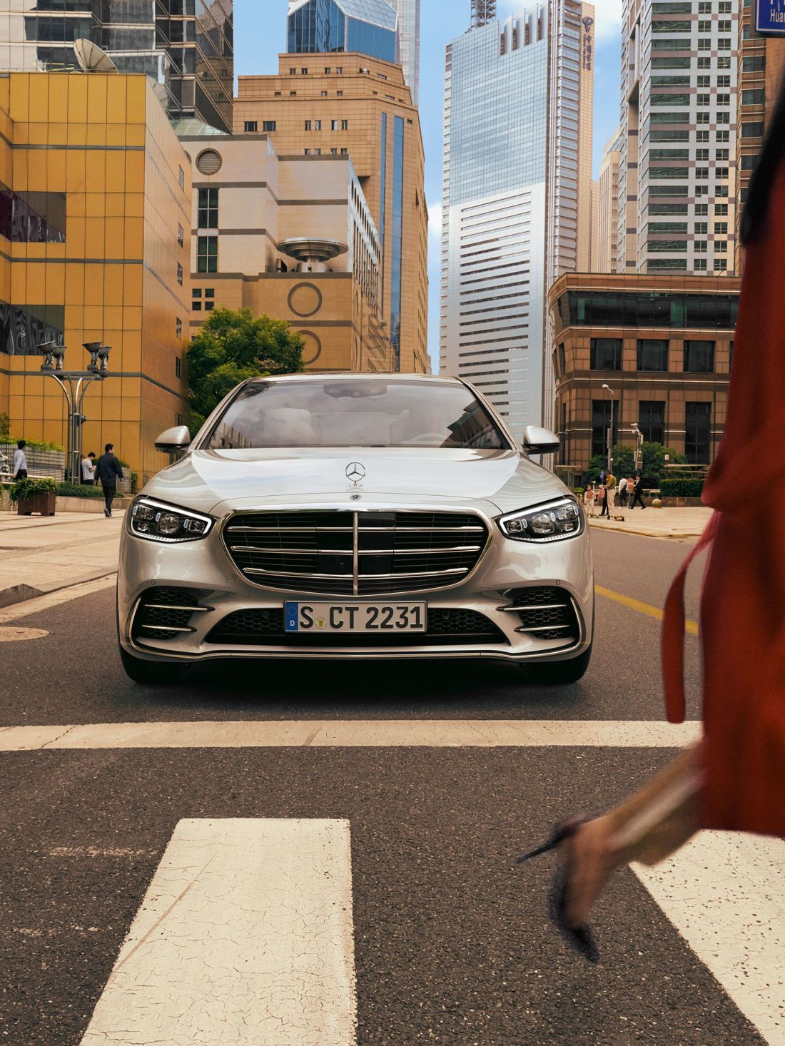 The new 2021 Mercedes-Benz S-Class Saloon (WV 223): The S-Class stands at a pedestrian crossing that is being crossed by two pedestrians.
