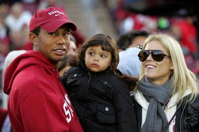 PALO ALTO, CA - NOVEMBER 21: Honorary Standford Cardinal captain Tiger Woods holds his daugher, Sam, and stands next to his wife, Elin Nordegren, on the sidelines before the Cardinal game against the California Bears at Stanford Stadium on November 21, 2009 in Palo Alto, California. (Photo by Ezra Shaw/Getty Images)