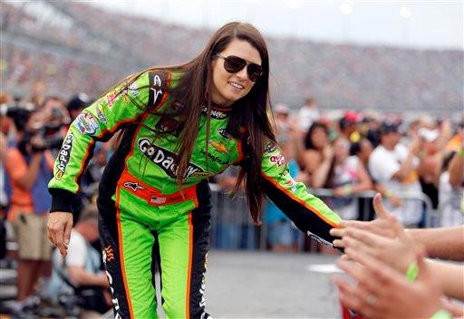 Danica Patrick high fives fans during driver introductions before the start of the NASCAR Sprint Cup series auto race at Darlington Raceway, in Darlington, S.C. New country music fan Patrick will co-host the American Country Awards Tuesday, Dec. 10, 2013, on FOX with Trace Adkins.