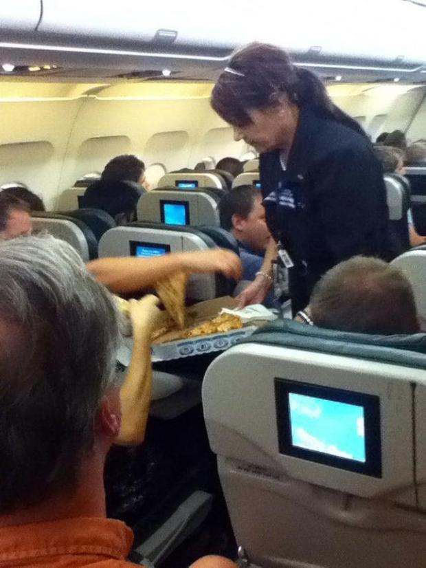 In this photo taken Monday, July 7, 2014, a Frontier Airlines flight attendant passes out pizza to passengers aboard a Denver-bound flight diverted to Cheyenne, Wyo. The airplane pilot treated his passengers to the pizza after they were diverted. (AP Photo/Logan Marie Torres)