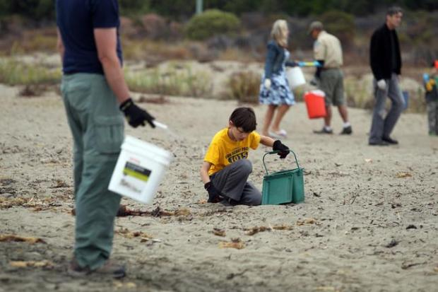 Dan Sykes, left, of Alameda, and his son Roman Sykes, 10, take part in the Coastal Cleanup Day at Crown Beach in Alameda, Calif., on Saturday, Sept. 20, 2014. The beach is cleaner than the past years, Dan said, who has volunteered for the last 25 years on and off. (Ray Chavez/Bay Area News Group)
