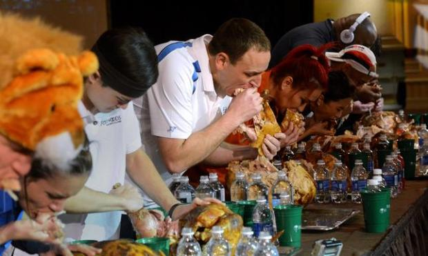 In this Nov. 22, 2014 photo, Joey Chestnut, center, and the other eaters participate in the World Turkey-Eating Championship at Foxwoods Resort and Casino in Mashantucket, Conn. Chestnut won the contest in Connecticut, setting a record by devouring an entire bird. (AP Photo/The Day, Dana Jensen) MANDATORY CREDIT