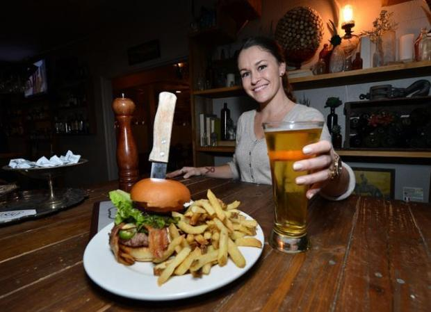 Hannah Wackerman serves up a beer to go with the Twisted Burger at the 1850 restaurant in Mariposa, Calif. on Wednesday, Jan. 7, 2015. (Kristopher Skinner/Bay Area News Group)