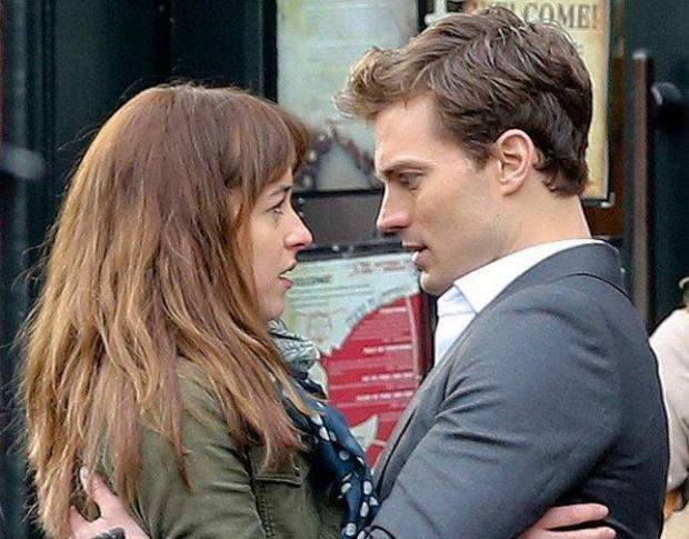 """Dakota Johnson and Jamie Dornan shoot a scene for the film """"Fifty Shades of Grey."""" (Focus Features)"""