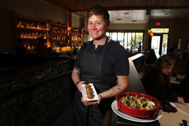 Executive chef Jen Biesty poses with bacalao croquetas and Manila clams and chorizo known as bomba at her new restaurant Shakewell in Oakland on Aug. 12, 2014.
