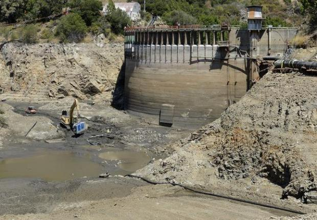 Granite Rock dewatering crew members remove a pump from an area formerly covered by water and debris as the San Clemente Dam removal project enters its third and final stage in Carmel Valley on June 12, 2015. (David Royal - Monterey Herald)
