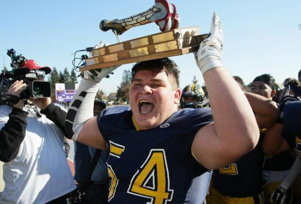 Lincoln High's Juan De La Cruz (54) proudly lifts the Big Bone trophy after the 73rd annual Big Bone Game between San Jose High School and Lincoln High School played at San Jose City College on Nov. 26, 2015, in San Jose.