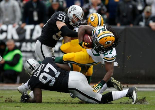 Oakland Raiders' Ben Heeney (51) and Mario Edwards Jr. (97) tackle Green Bay Packers' Eddie Lacy (27) in the first quarter of their NFL game at O.co Coliseum in Oakland, Calif, on Sunday, Dec. 20, 2015. (Nhat V. Meyer/Bay Area News Group)