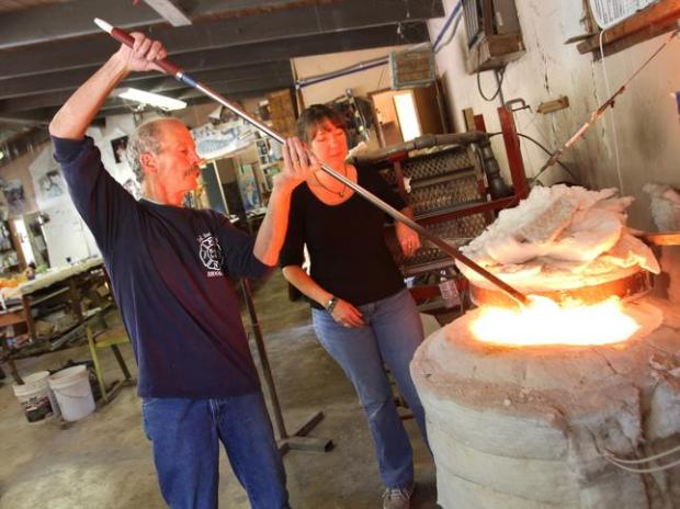 "Tom Stanton scoops up a wad of molten glass from the ""glory hole"" with assistance from Shannon Lovelace. The legendary glass blower of Holy City Glass died in October of 2015. (George Sakkestad/Staff archives)"