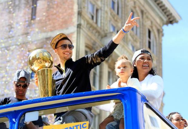MVP Stephen Curry and his family reaches to the roar of the crowd along the parade route on Broadway in Oakland, Calif., on Friday, June 19, 2015. Thousands of fans line the streets in Oakland to celebrate and honor the NBA Champions Golden State Warriors. (Laura A. Oda/Bay Area News Group)