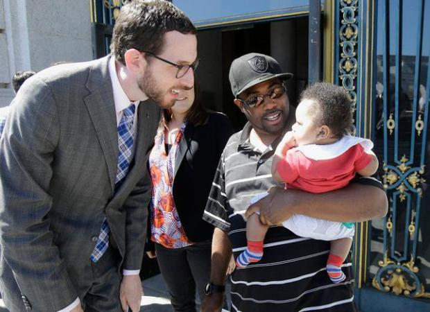 Alphonzo Jackson, center, holds his six-month old son Isaiah as he speaks with San Francisco Supervisor Scott Wiener, left, before a rally supporting paid family leave at City Hall in San Francisco, Tuesday, April 5, 2016. The San Francisco Board of Supervisors is voting on whether to require six weeks of fully paid leave for new parents - a move that would be a first for any jurisdiction. (AP Photo/Jeff Chiu)