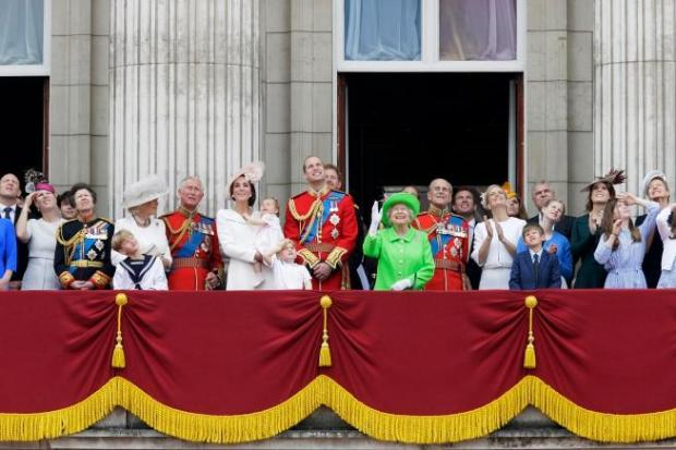 """Britain's Queen Elizabeth II waves as she watches the flypast, with Prince Philip, to right, Prince William, centre, with his son Prince George, front, Kate, Duchess of Cambridge holding Princess Charlotte, centre left, with The Prince of Wales standing with The Duchess of Cornwall, and Princess Anne, 4th left, on the balcony during the Trooping The Colour parade at Buckingham Palace, in London, Saturday, June 11, 2016. Hundreds of soldiers in ceremonial dress have marched in London in the annual Trooping the Colour parade to mark the official birthday of Queen Elizabeth II. The Trooping the Colour tradition originates from preparations for battle, when flags were carried or """"trooped"""" down the rank for soldiers to see. (AP Photo/Tim Ireland)"""