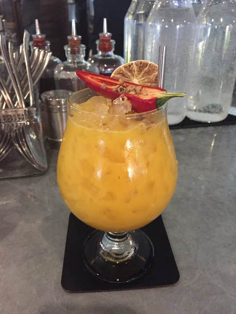 The Pony Express, topped with half a red pepper and containing flavors of banana, coconut and tumeric, is one of the inventive cocktails on the menu at Orchard City Kitchen at the Pruneyard in Campbell. (Sal Pizarro/Staff)