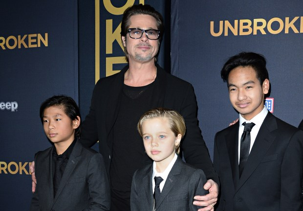 """(FILES) This file photo taken on December 15, 2014 shows actor Brad Pitt and children Pax Jolie-Pitt (L), Shiloh Jolie-Pitt (C) and Maddox Jolie-Pitt as they arrive for the US premiere of Universal Pictures """"Unbroken,"""" at the Dolby Theatre in Hollywood, California. Brad Pitt is under investigation by US authorities after being accused of physically and verbally abusing his children during an angry outburst, TMZ reported September 22, 2016. According to the entertainment news site the Los Angeles Police Department began probing Pitt based on an anonymous tip received by the LA County Department of Children and Family Services, as is systematic following any report of child abuse. / AFP PHOTO / ROBYN BECKROBYN BECK/AFP/Getty Images"""