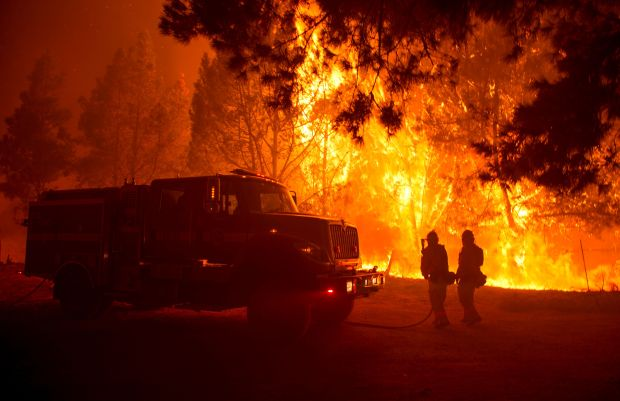 Firefighters attempt to push back flames in the Santa Cruz Mountains near Loma Prieta, California on September 27, 2016. The Loma Prieta Fire has charred more than 1,000 acres and burned multiple structures in the area. / AFP PHOTO / Josh EdelsonJOSH EDELSON/AFP/Getty Images