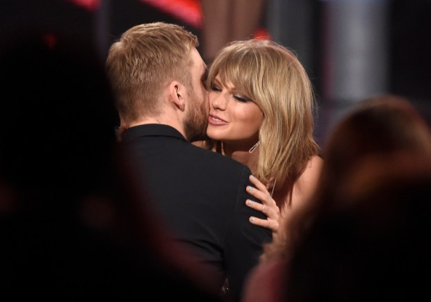 """FILE - In this May 17, 2015 file photo, Taylor Swift, right, hugs Calvin Harris after winning the award for top billboard 200 album for """"1989"""" at the Billboard Music Awards at the MGM Grand Garden Arena in Las Vegas. Swift has confirmed that she co-wrote ex-boyfriend's Calvin Harris' latest hit song under an alias, which prompted the DJ-producer to send a series of angry tweets Wednesday, July 13, 2016. (Photo by Chris Pizzello/Invision/AP)"""