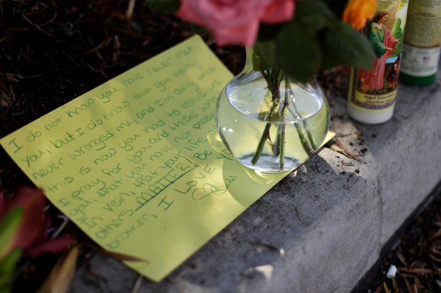 """A note and flowers sit along the edge of a parking lot Wednesday, Sept. 28, 2016, in El Cajon, Calif, near where a man was killed Tuesday. A black man reportedly acting erratically at a strip mall in El Cajon was shot and killed Tuesday by police after pulling an object from his pocket, pointing it at officers and assuming a """"shooting stance,"""" authorities said. (AP Photo/Gregory Bull)"""