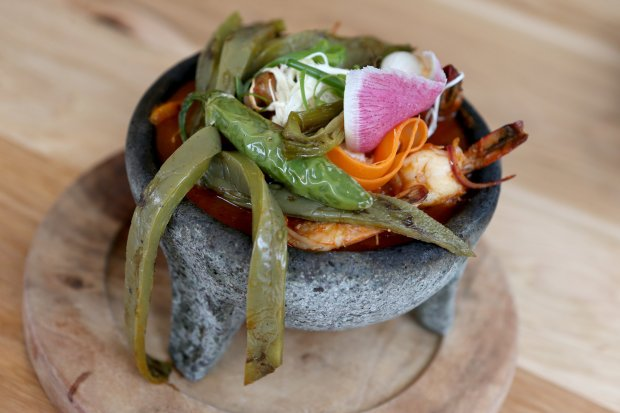 The Molcajete, tasajo, grilled chicken, prawns, grilled onions and peppers, nopal and quesillo is photographed at Agave Uptown in Oakland, Calif., on Thursday, Sept. 1,2016. (Anda Chu/Bay Area News Group)
