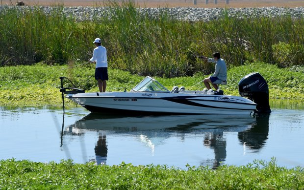 Along the calm waters of the Delta, two men try their luck fishing from a boat at Holland Tract, Calif., on Sunday, Sept. 25, 2016. Warm temperatures lured many outside to enjoy the day. (Susan Tripp Pollard/Bay Area News Group)