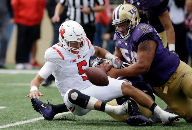 Rutgers quarterback Chris Laviano (5) fumbles the ball while being sacked by Washington's Vita Vea, right, and Azeem Victor in the first half of an NCAA college football game Saturday, Sept. 3, 2016, in Seattle. Rutgers recovered the ball on the play. (AP Photo/Elaine Thompson)