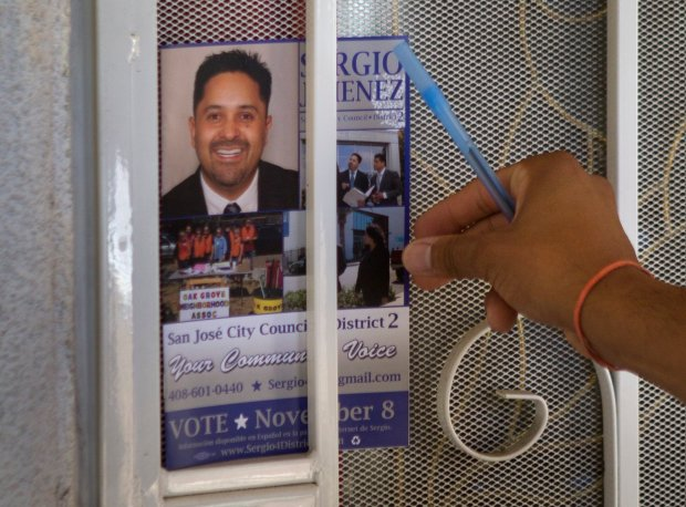 San Jose City Council candidate, Sergio Jimenez, puts a flyer in a door as he canvases a neighborhood in San Jose, Calif., Friday, Sept. 16, 2016. Jimenez is running against Steve Brown for the San Jose District 2 City Council seat in November. (Patrick Tehan/Bay Area News Group)