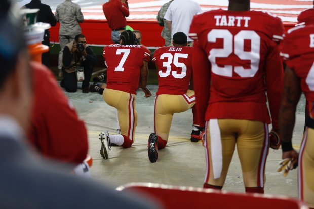 49ers quarterback Colin Kaepernick (7) and safety Eric Reid (35) kneel during the national anthem Monday at the 49ers opener, and they did so again Sunday in Charlotte. (Nhat V. Meyer/Bay Area News Group)