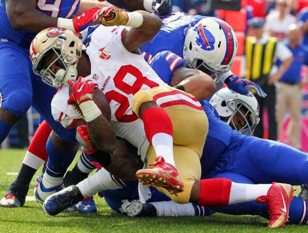 San Francisco 49ers running back Carlos Hyde (28) is tackled by Buffalo Bills defenders during the first half of an NFL football game on Sunday, Oct. 16, 2016, in Orchard Park, N.Y. (AP Photo/Bill Wippert)