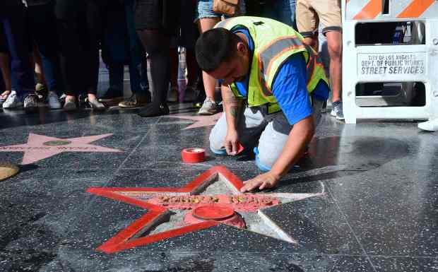 TOPSHOT - A crowd gathers to watch as Donald Trump's vandalized Star along the Hollywood Walk of Fame is tended to and cleaned up before being replaced on October 26, 2016 in Hollywood, California. A man defaced Republican presidential candidate Donald Trump's star on the Hollywood Walk of Fame Wednesday, hacking out the gold lettering displaying his name and the television logo. A man who identified himself to a local news agency as James Lambert Otis, said he vandalized the tribute with a sledgehammer and pickaxe, originally intended to remove the entire star from the sidewalk on Hollywood Boulevard. / AFP PHOTO / Frederic J. BROWNFREDERIC J. BROWN/AFP/Getty Images