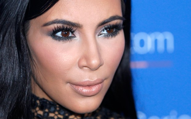 "FILE - In this June 24, 2015, file photo, Kim Kardashian poses during a photo call at the Cannes Lions 2015. A spokeswoman for Kardashian West says she was held up at gunpoint inside her Paris hotel room Sunday, Oct. 2, 2016, by two armed masked men dressed as police officers. The representative said the reality TV star is ""badly shaken but physically unharmed."" She offered no other details. (AP Photo/Lionel Cironneau, File)"