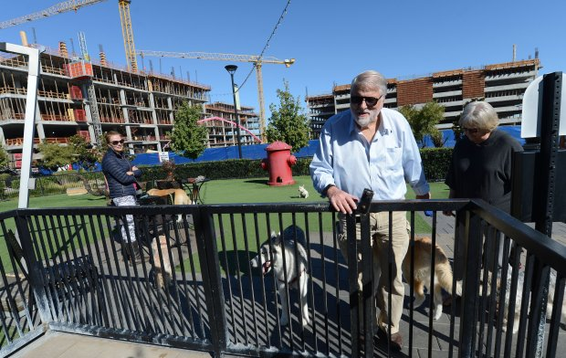 "As construction continues, Stephen and Inger Borgess, of Los Altos, leave a dog park that is part of The Villages in Mountain View, Calif., on Wednesday, Oct. 26, 2016. This new architectural trend know as ""city centers"" or ""lifestyle centers"" has caught on all over the Bay Area, mixing residential, retail, restaurants, hotels and the like all around town squares. (Dan Honda/Bay Area News Group)"