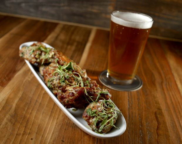 The green curry chicken wings and a pint of Speakeasy's Big Daddy IPA are photographed at the Beer Baron Bar and Kitchen in Pleasanton, Calif., on Tuesday, Oct. 25, 2016. (Anda Chu/Bay Area News Group)