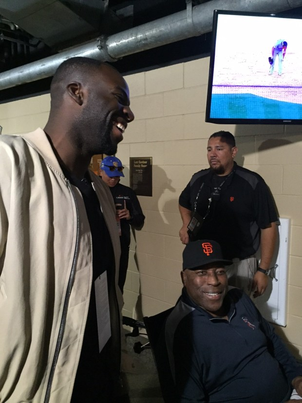 Draymond Green of the Golden State Warriors meets up with Giants' legend Willie McCovey outside the home clubhouse at AT&T Park before Game 4 of the National League Division Series.. (Photo by Mark Purdy)