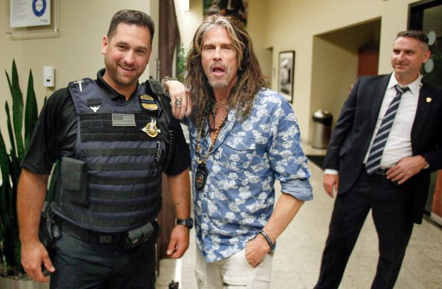Singer-songwriter Steven Tyler poses for photos with security officers following a visit with President Barack Obama aboard Air Force One in Orlando, Fla., Friday, Oct. 28, 2016. (AP Photo/Reinhold Matay)