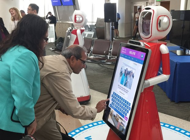 Modasser Hussain, who was traveling from San Jose back home to upstate New York, interacts with one of the new robots introduced to help travelers at Mineta San Jose International Airport on Tuesday, Oct. 25, 2016. (Sal Pizarro/Bay Area News Group)