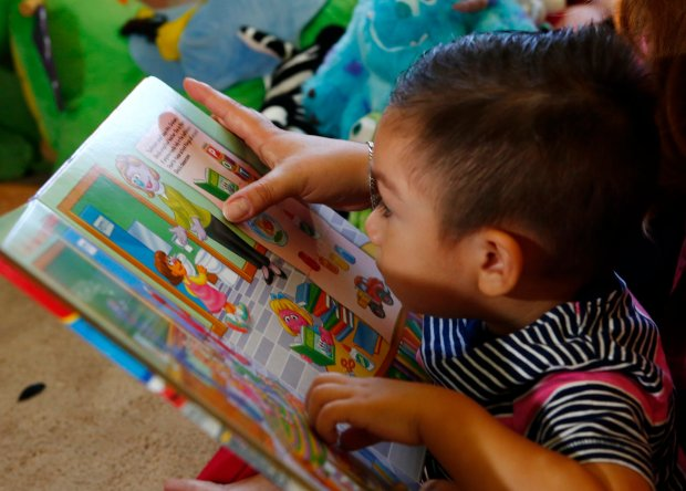 One-year-old, Matias Palma, listens to a story read by his mother, Jetzabel Gonzalez, at their home in San Jose, Calif., on Wednesday, Oct. 26, 2016. Gonzales participates in the NuParent Program at Grail Family Services which helps Spanish-speaking immigrants to give their kids a strong start to a lifetime of learning. (Gary Reyes/Bay Area News Group)