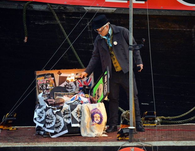 Joe Corre, the son of Vivienne Westwood and Sex Pistols creator Malcolm McLaren, burns his £5 million punk collection on a boat on the River Thames in London, Saturday, Nov. 26, 2016. (Dominic Lipinski/PA via AP)