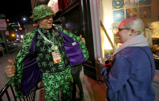 """Doorman """"Big Mike,"""" of Oakland, right, and Lauren Phillips, of San Francisco, celebrate during a Proposition 64 election night party at The New Parish nightclub in Oakland, Calif., on Tuesday, Nov. 8, 2016. The proposition would legalize the recreational use of marijuana in the state. (Jane Tyska/Bay Area News Group)"""