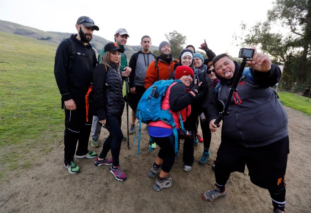 Eder Castro from San Bruno, right, takes a group selfie with the attendees of a pop-up hike at the trail head at Mission Peak in Fremont, Calif., on Friday, Nov. 25, 2016. Castro hosted the hike as part of the @52HikeChallenge in partnership with REI , encouraging people to spend the day outside as an alternative to the Black Friday shopping chaos. (Laura A. Oda/Bay Area News Group)