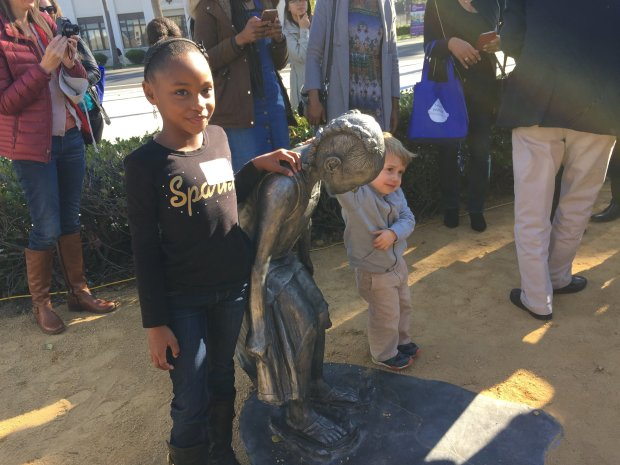 Jayla Hughes, 7, and 2-year-old Henry Carrington pose with the aluminum sculpture Jayla was the model for that is now part of the Rotary Children's Sculpture Walk in San Jose's Guadalupe River Park.