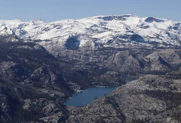 In this April 28, 2015, file photo, a Sierra Nevada lake in California is surrounded by barren ridges, usually covered in snow that time of year, during an aerial survey of the snowpack done by the California Department of Water Resources. The far western United States set records for low snowpack levels in 2015, and a new report blames high temperatures rather than low precipitation levels. (Rich Pedroncelli, File AP Photo)