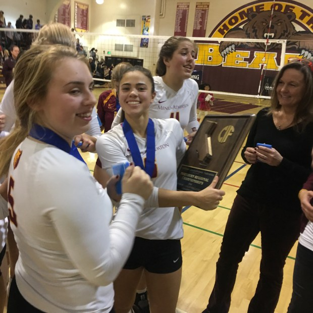 Menlo-Atherton senior Jacqueline DiSanto holds the NorCal Division I girls volleyball championship trophy.