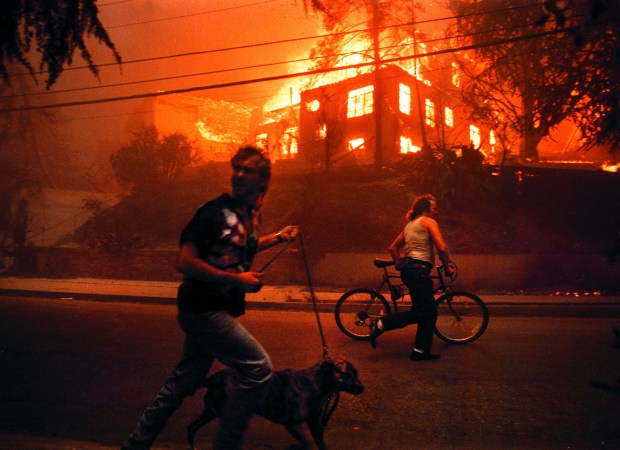 Residents flee Broadway Terrace past a burning home at 5974 Buena Vista Avenue during a huge firestorm in Oakland, Calif. Sunday Oct. 20, 1991. (Karl Mondon/Staff) NOTE: Scans made from negatives in 2011 for 20th anniversary project.
