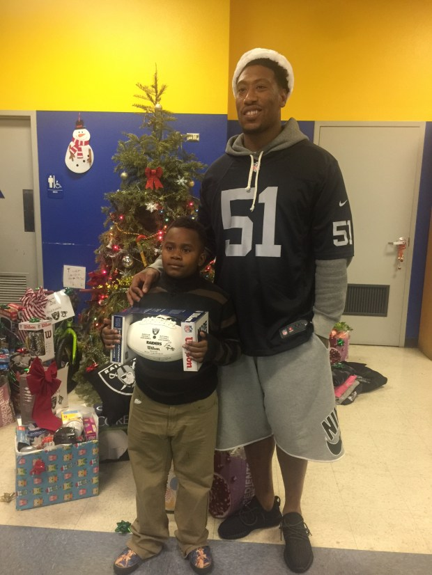 "Raiders linebacker Bruce Irvin poses with Oakland Boys and Girls Club member Johnathan Abraham at Dan Williams' ""Filling the Gap"" Foundation event on Tuesday."
