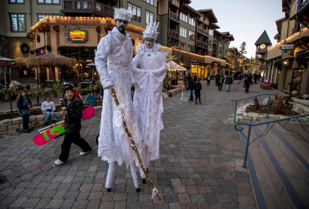 A snowboarder looks up as members of Stilt Circus pose for a portrait at The Village at Mammoth during Night of Lights celebration and the 60th anniversary of Mammoth Mountain ski area in Mammoth Lakes in December.(Mark Rightmire, ORANGE COUNTY REGISTER)