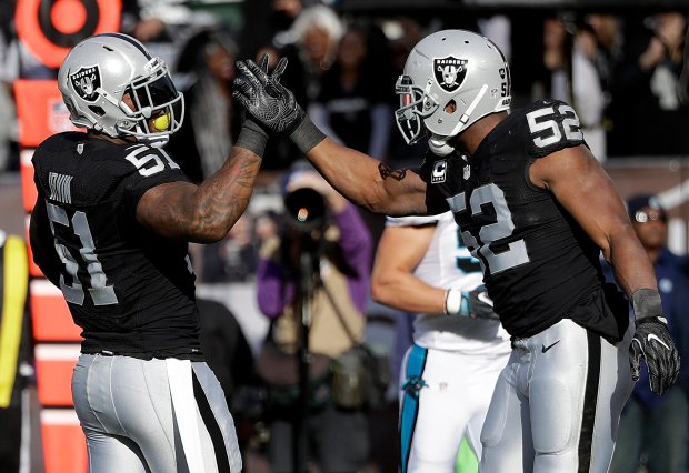 Oakland Raiders outside linebacker Bruce Irvin (51) is congratulated by defensive end Khalil Mack (52) after sacking Carolina Panthers quarterback Cam Newton during the first half of an NFL football game in Oakland, Calif., Sunday, Nov. 27, 2016. (AP Photo/Marcio Jose Sanchez)