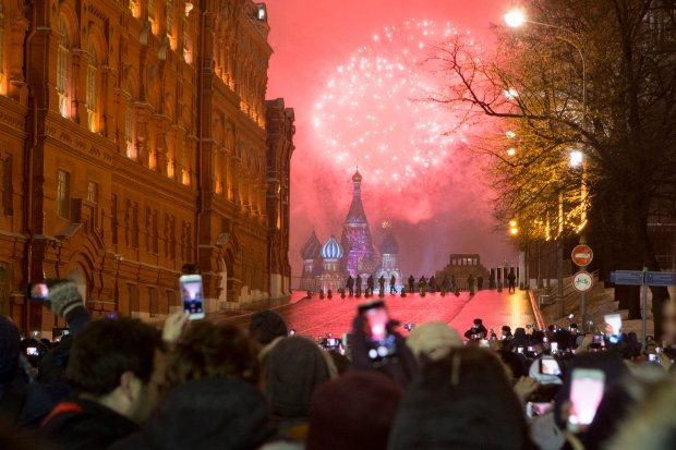 People watch as fireworks explode over the Kremlin standing at Red Square blocked by police during New Year celebrations in Moscow, Russia, Sunday, Jan. 1, 2017. New Year's Eve is Russia's major gift-giving holiday, and big Russian cities were awash in festive lights and decorations. (AP Photo/Alexander Zemlianichenko Jr)