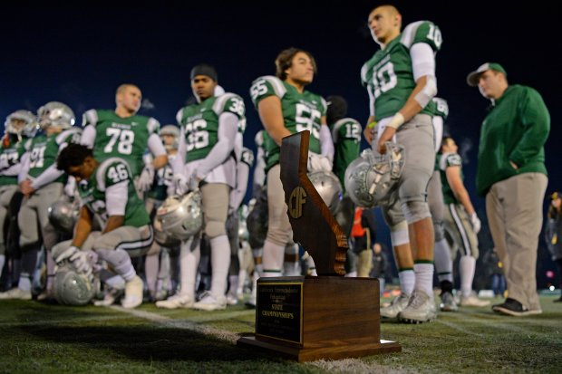 The second place trophy rests on the field as the De La Salle Spartans watch the St. John Bosco team accept the first place trophy after being defeated during the 2016 CIF State Football Championship Open Division game at Hornet Stadium at Sacramento State University in Sacramento, Calif. on Saturday, Dec. 17, 2016. St. John Bosco defeated the De La Salle Spartans 56-33. This was the most points scored against De La Salle since 1979. (Jose Carlos Fajardo/Bay Area News Group)
